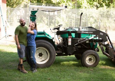 Emily and her husband in front of a tractor