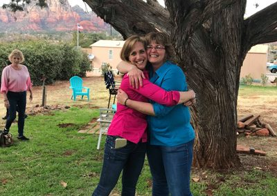 Two women hugging in front of a tree