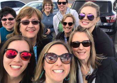 Group selfie of women in a parking lot.